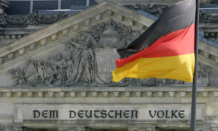 The German national flag waves beside the main entrance of the Reichstag's building, the seat German lower house of parliament Bundestag in Berlin, June 30, 2005. German Chancellor Gerhard Schroeder will abstain from voting in the Friday confidence vote in parliament he hopes will pave the way to new elections. The inscription on the building reads: 'For the German people'. REUTERS/Fabrizio Bensch  FAB/CVI - RTRFYPT